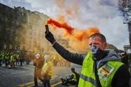 PARIS, FRANCE - MARCH 09: A Gilet Jaune or Yellow Vest protestor holds an orange flare aloft during Act 17 of protests on the Champs Elysees on March 09, 2019 in Paris, France. For the first time, the protesters intend to demonstrate all weekend in a hope to revive the movement that is in decline ahead of the end of President Macron's 'Great National Debate' next week. (Photo by Kiran Ridley/Getty Images)