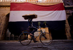 A vendor carries bread tray as he cycles, in front of a giant Egyptian flag, in Cairo, Egypt, Friday, Nov. 17, 2017. (AP Photo/Amr Nabil)