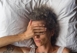 High angle close up  view of middle aged woman sleeping on pillow with hand over eyes (selective focus)