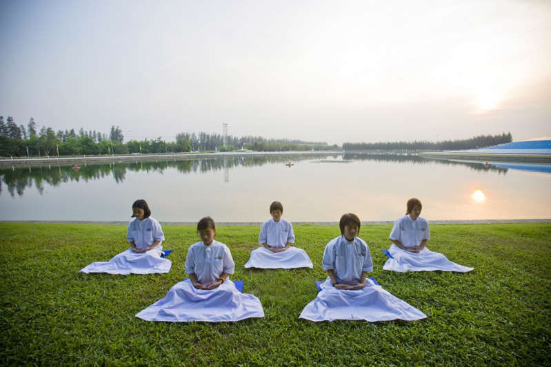 a group of people sitting in front of a body of water: meditation | Longevity LIVE