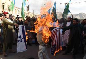 Protesters burn an effigy depecting US President Donald Trump during an anti-US and Israel protest in Quetta on December 8, 2017.