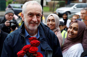 Britain's opposition Labour Party leader, Jeremy Corbyn, is greeted by young women and red roses during a visit to Finsbury Park Mosque, on Visit My Mosque day, in London, Britain, March 3, 2019. REUTERS/Peter Nicholls
