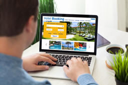man typing laptop keyboard with online search booking hotel on screen in room