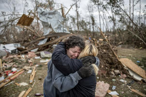 "Carol Dean, left, cries while embraced by Lawanda Anderson as Dean sifts through the debris of the home she shared with her husband, David Wayne Dean, who died when a tornado destroyed the house in Beauregard, Ala., Monday, March 4, 2019. ""He was my wedding gift,"" said Dean of her husband whom she married three years ago. ""He was one in a million. He'd send me flowers to work just to let me know he loved me. He'd send me some of the biggest strawberries in the world. I'm not going to be the same."""