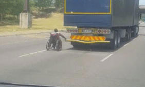 Man in Wheelchair Grips Back of Truck as it Speeds Down South African Highway