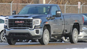a truck is parked in front of a car: GMC Sierra HD Regular Cab Spy Shots
