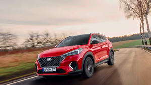 a red car parked on the side of a road: 2019 Hyundai Tucson N Line