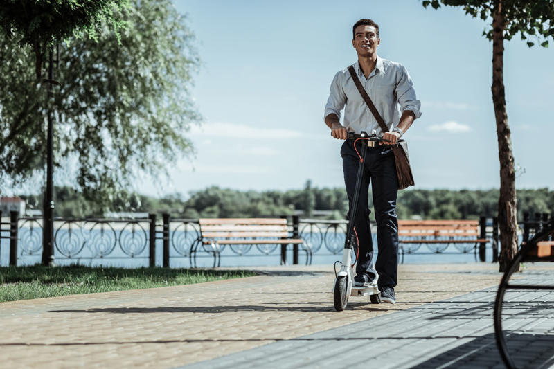 Ecological and quick. Low angle of exuberant handsome guy riding electric scooter and grinning