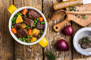 Beef and vegetable stew with potatoes on rural table viewed from above