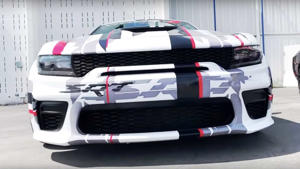 a white and black truck sitting on top of a car: The Dodge Charger Widebody Concept has been spotted at the SoCal LX Spring Fest 14.