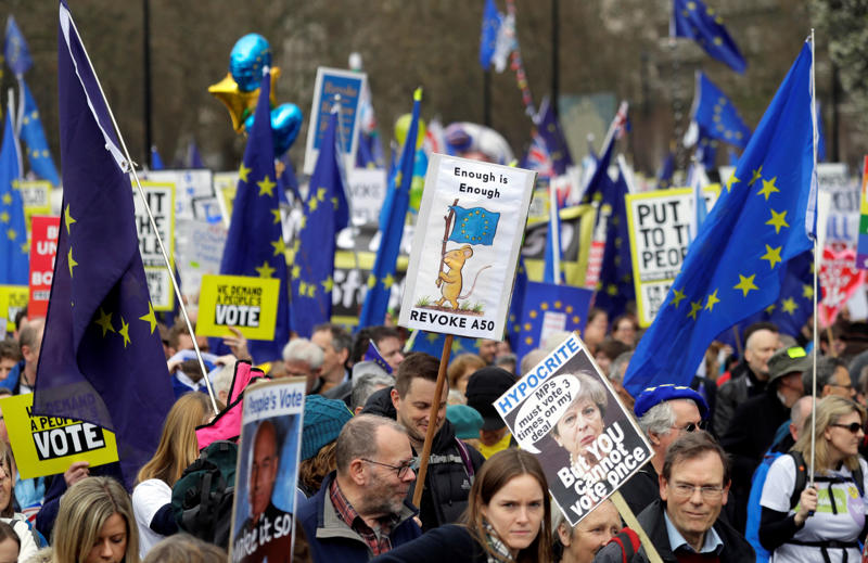 Demonstrators carry posters during a Peoples Vote anti-Brexit march in London, Saturday, March 23, 2019. The march, organized by the People's Vote campaign is calling for a final vote on any proposed Brexit deal. This week the EU has granted Britain's Prime Minister Theresa May a delay to the Brexit process. (AP Photo/Kirsty Wigglesworth)