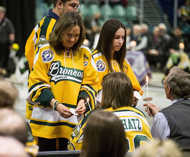 c0405ba7ad09 Family members and friends light candles during the Humboldt Broncos  memorial service at Elgar Petersen Arena
