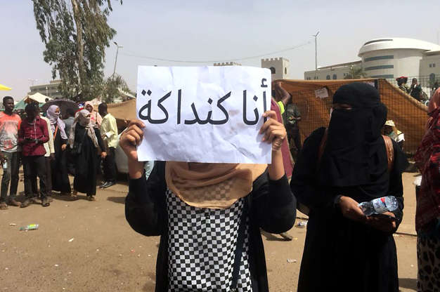 Slide 3 of 18: A Sudanese demonstrator holds a slogan reading in Arabic: 'I am a 'kandake' (Meroitic language term for queen) during a rally in front of the military headquarters in the capital Khartoum on April 10, 2019. - Thousands of protesters have been camping outside the military complex housing Bashir's official residence in Khartoum since April 6, braving tear gas and deadly gun shots from security services in defiance of a state of emergency banning all such demonstrations. The army, which has steered clear of intervening in the clashes since the start of the anti-government protests in December, has so far stood on the sidelines. (Photo by - / AFP)        (Photo credit should read -/AFP/Getty Images)
