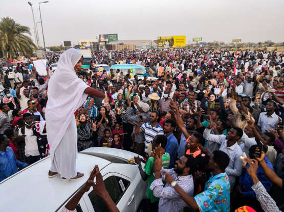 Slide 2 of 18: Alla Salah, a Sudanese woman propelled to internet fame earlier this week after leading powerful protest chants against President Omar al-Bashir, addresses protesters during a demonstration in front of the military headquarters in the capital Khartoum on April 10, 2019. - In the clips and photos, the elegant Salah stands atop a car wearing a long white headscarf and skirt as she sings and works the crowd, her golden full-moon earings reflecting light from the fading sunset and a sea of camera phones surrounding her. Dubbed online as 'Kandaka', or Nubian queen, she has become a symbol of the protests which she says have traditionally had a female backbone in Sudan. (Photo by - / AFP)        (Photo credit should read -/AFP/Getty Images)