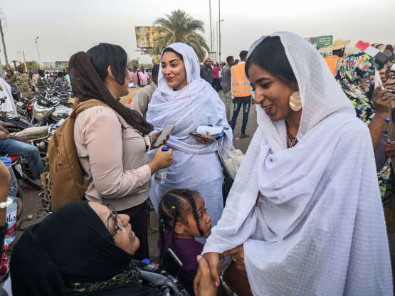 Slide 1 of 18: Alaa Salah, a Sudanese woman propelled to internet fame earlier this week after clips went viral of her leading powerful protest chants against President Omar al-Bashir, shakes hands with a protester during a demonstration in front of the military headquarters in the capital Khartoum on April 10, 2019. - In the clips and photos, the elegant Salah stands atop a car wearing a long white headscarf and skirt as she sings and works the crowd, her golden full-moon earings reflecting light from the fading sunset and a sea of camera phones surrounding her. Dubbed online as 'Kandaka', or Nubian queen, she has become a symbol of the protests which she says have traditionally had a female backbone in Sudan. (Photo by - / AFP)        (Photo credit should read -/)