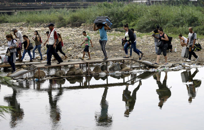 Slide 4 of 65: Venezuelans cross illegally into Colombia near the Simon Bolivar International Bridge, top, which is partially closed by Venezuelan authorities who are only permitting students, seniors and the sick to cross, seen from La Parada near Cucuta, Colombia, Sunday, April 14, 2019. U.S. Secretary of State Mike Pompeo is making the economic and political crisis in Venezuela a central theme of his four-day Latin America tour.