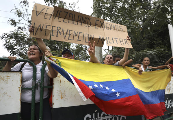 "Slide 3 of 65: People hold a Venezuelan flag and the Spanish message: ""Venezuelans demand military intervention,"" on the sidelines of a visit by U.S. Secretary of State Mike Pompeo in La Parada near Cucuta, Colombia, on the border with Venezuela, Sunday, April 14, 2019. Vice President Mike Pence said on Wednesday, April 10 to the U.N. Security Council that the Trump administration is determined to remove Venezuelan President Nicolas Maduro from power, preferably through diplomatic and economic pressure, but repeated the apparent threat of military action by adding that ""all options are on the table."""