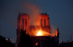 Firefighters douse flames of the burning Notre Dame Cathedral in Paris.
