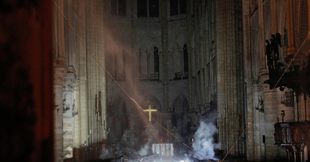 a blurry photo of an old building: Smoke around the altar inside the cathedral on Tuesday.