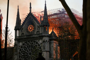 Flames and smoke are seen billowing from the roof at Notre-Dame Cathedra.