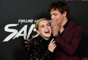 "Kiernan Shipka, left, and Ross Lynch, cast members in ""Chilling Adventures of Sabrina,"" share a laugh at the premiere of the Netflix series, Friday, Oct. 19, 2018, in Los Angeles. (Photo by Chris Pizzello/Invision/AP)"