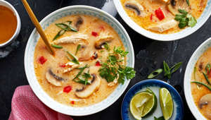 a bowl of food on a plate: Coconut milk tames the heat and combines deliciously with shredded chicken breast in Spicy Thai Coconut Chicken Soup.