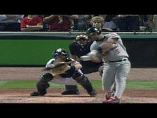 a baseball player swinging a bat at a ball: 10/17/05: Albert Pujols hits a long three-run home run in the ninth to give the Cardinals the lead