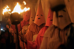 Hooded catholic faithful representing Roman soldiers, known as 'Farricocos', carry flaming torches during the annual Fogareu Holy Week procession in Goias, 350 km west of Brasilia, Brazil, early on April 18, 2019. - The Christian religious ceremony is a re-enactment of the arrest of Jesus Christ. The costumes are of medieval origin, and were used by penitents so they could atone for their sins without having to reveal their identity in public. (Photo by CARL DE SOUZA / AFP)        (Photo credit should read CARL DE SOUZA/AFP/Getty Images)