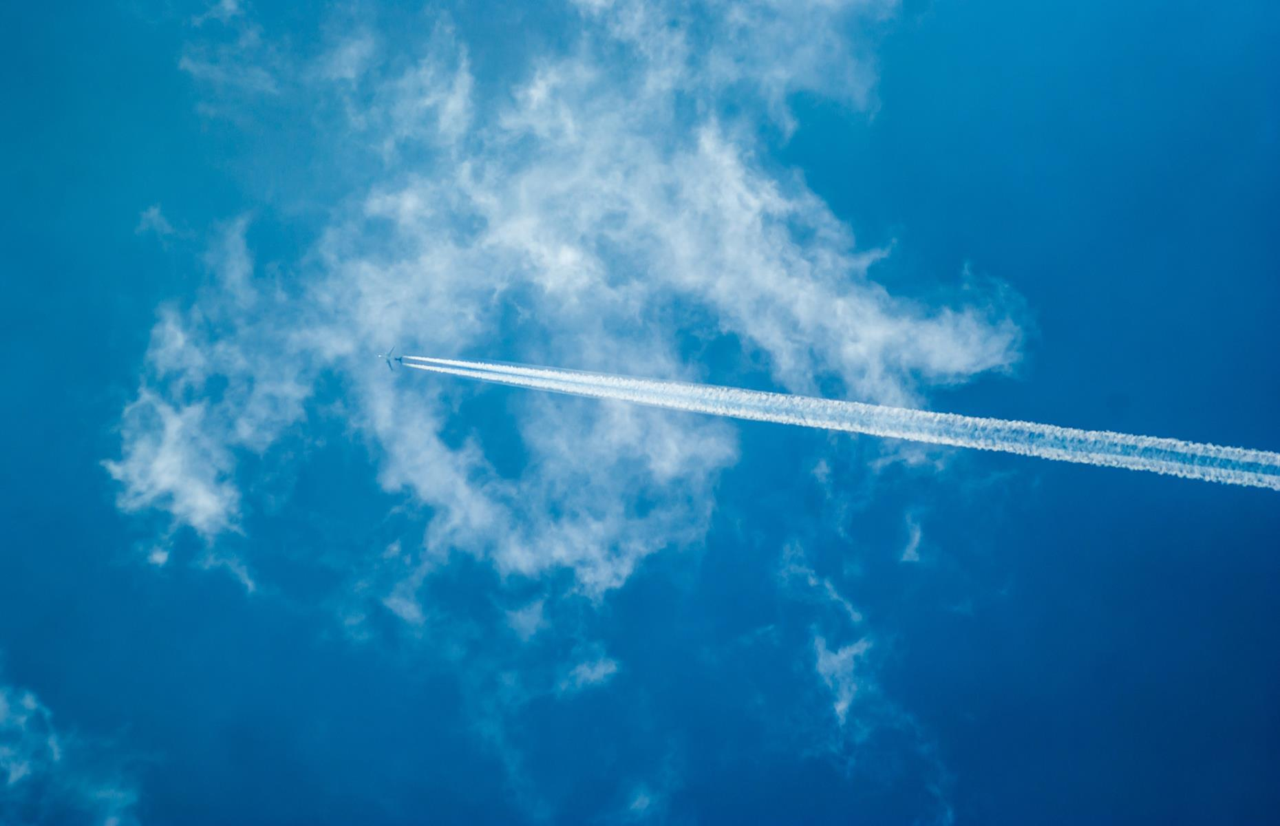 Slide 7 of 63: Those white tracks in the sky are called contrails and there's some science behind them. When a plane is in flight, its hot exhaust mixes with the surrounding atmosphere which, at high altitude, is much colder and thinner than the plane's emissions. This causes the water vapor in the exhaust to freeze, leaving icy streaks across the sky.