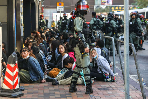 Slide 1 of 50: People are detained by police near the Hong Kong Polytechnic University in Hung Hom district of Hong Kong on November 18, 2019. - Pro-democracy demonstrators holed up in a Hong Kong university campus set the main entrance ablaze November 18 to prevent surrounding police moving in, after officers warned they may use live rounds if confronted by deadly weapons.