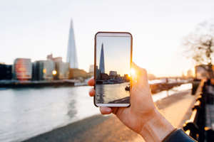 A man takes a photo of the London skyline with his smartphone