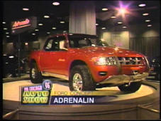a car parked on the side of a building: Mark Giangreco, WLS-TV lead sports anchor and co-host of the 1996 Chicago Auto Show narrates on eight concept vehicles on exhibit.  Two North America debuts included the Honda SSM (Sport Study Model) Roadster and Isuzu Deseo prototypes. Audi displayed the TTS Roadster and Chrysler their LHX concept. Ford Motor Co. brought four experimental vehicles: Ford Ranger Adrenalin, Ford Synergy 2010, Ford V-12 Indigo and Lincoln Sentinel.