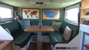 a room filled with furniture and a large window: Unicat Expedition RV