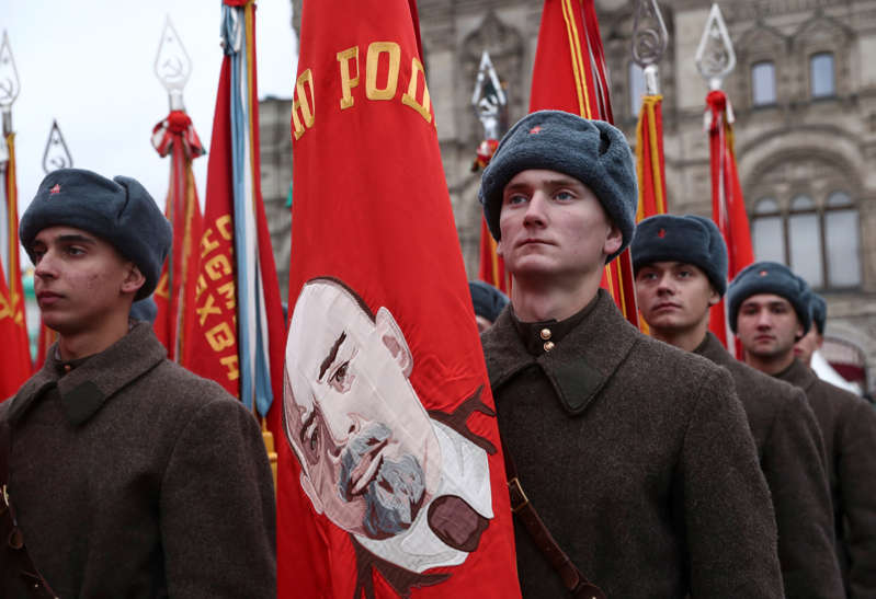 A participant holds a flag displaying an image of Soviet state founder Vladimir Lenin during preparations for a military parade to mark the anniversary of a historical parade in 1941, when Soviet soldiers marched towards the front lines during World War Two, on Red Square in central Moscow, Russia November 7, 2019.