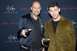 a man standing in front of John Varvatos, Nick Jonas posing for the camera: Dimitrios Kambouris/Getty Images for Revlon