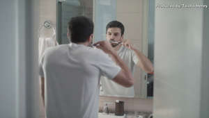 a man brushing his teeth in front of a mirror