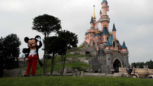 Mickey Mouse poses in front of the castle of Sleeping Beauty at Disneyland Paris, in Chessy, France, east of Paris, Saturday, June 8, 2018.
