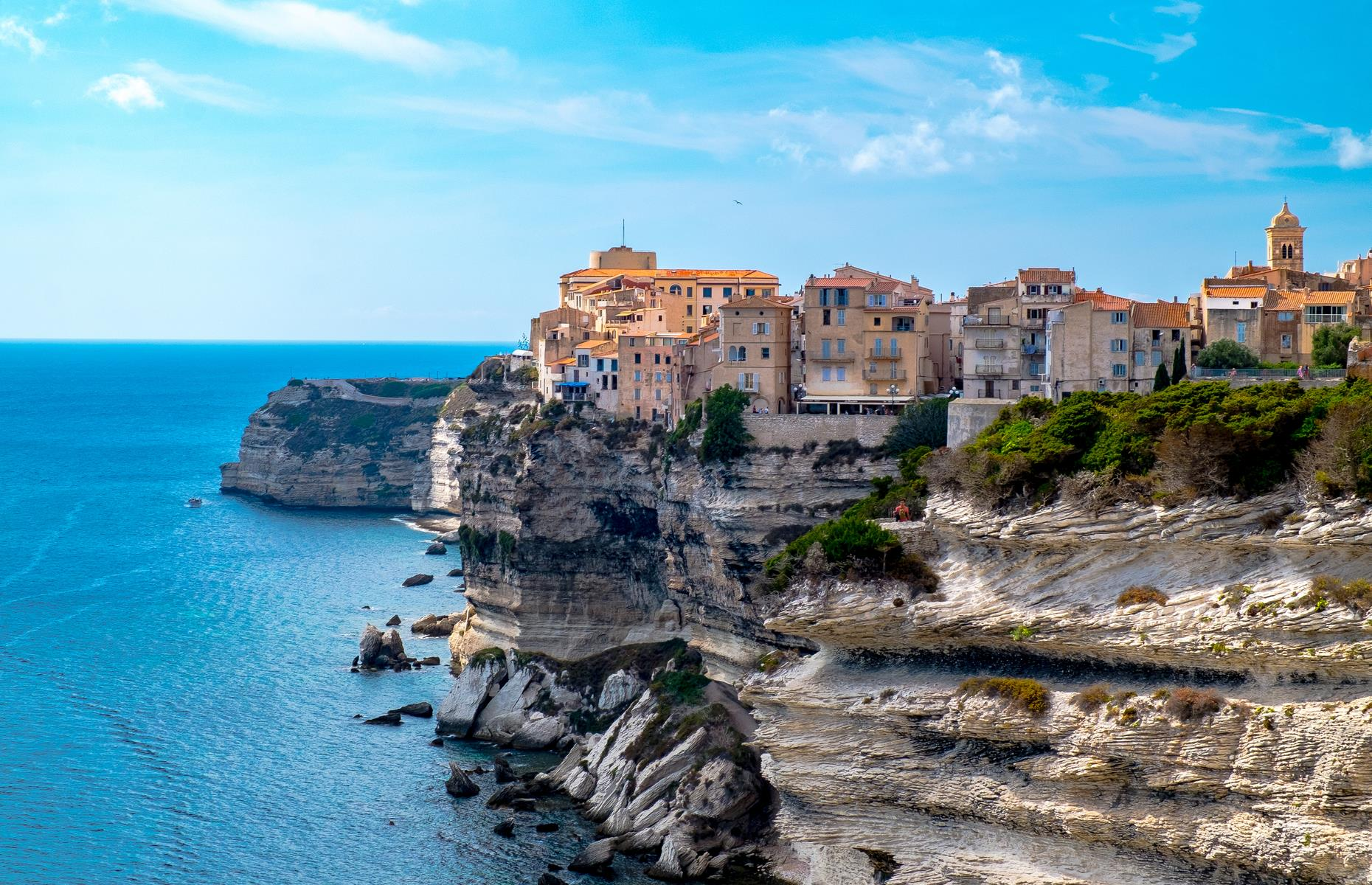 Slide 31 of 41: Dramatically poised on Corsica's rugged limestone cliffs, many of Bonifacio's buildings look like they're almost suspended over the sea below. Explore the town's meandering cobbled streets and take a walk to Capo Pertusato lighthouse, where you'll find staggering views over the glistening waters. If you fancy a dip, take a hike along the coastal path to L'Arinella, a pretty beach where you'll find peace and quiet aplenty.   Find more of the world's most stunning clifftop towns here
