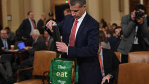 a man wearing a suit and tie: Stephen Castor, Minority Counsel for House Judiciary and House Permament Select Committee on Intelligence checks a bag on Capitol Hill in Washington,DC on December 9, 2019, during a House Judiciary Committee hearing on the grounds for the impeachment of President Donald Trump.