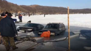 Russian fisherman pull cars from the icy sea