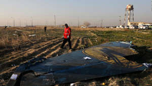 a person walking down a dirt road: A rescue worker searches the scene where a Ukrainian plane crashed in Shahedshahr southwest of the capital Tehran, Iran, Wednesday, Jan. 8, 2020. A Ukrainian airplane carrying 176 people crashed on Wednesday shortly after takeoff from Tehran's main airport, killing all onboard.