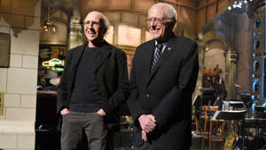 "Larry David in a suit standing in front of a building: SATURDAY NIGHT LIVE -- ""Larry David"" Episode 1695 -- Pictured: (l-r) Larry David and Senator Bernie Sanders introduce musical guest The 1975 on February 6, 2016 -- (Photo by: Dana Edelson/NBC/NBCU Photo Bank via Getty Images)"