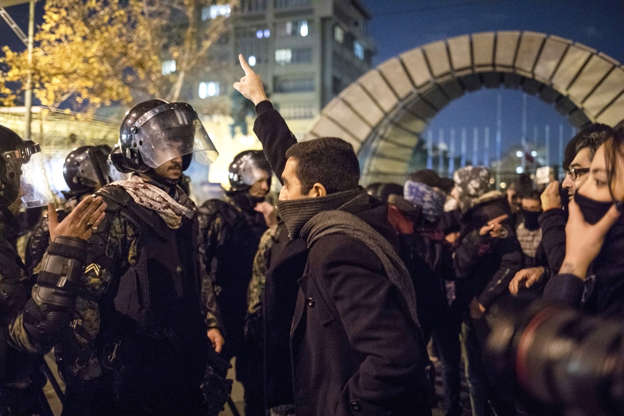 Slide 4 of 50: An Iranian man confronts riot police during a demonstration outside Tehran's Amir Kabir University on January 11, 2020.