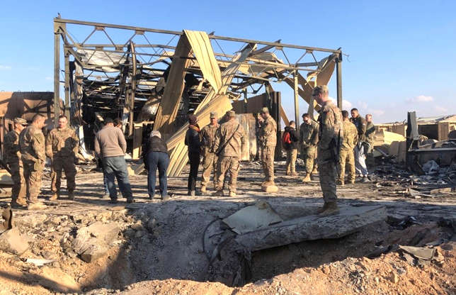 Slide 1 of 50: U.S. Soldiers stand at a site of Iranian bombing at Ain al-Asad air base in Anbar, Iraq, Monday, Jan. 13, 2020.