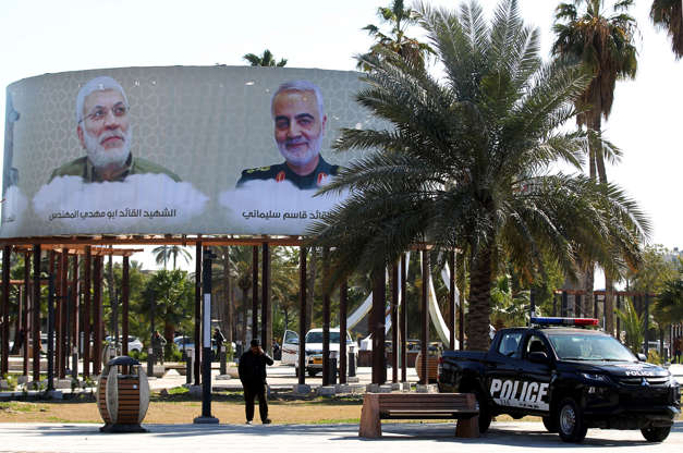 Slide 3 of 48: This picture taken on February 10, 2020 in the Iraqi capital Baghdad's district of Karrada shows an Iraqi police vehicle parked beneath mourning billboards on display, depicting top Iranian general Qasem Soleimani and Iraqi paramilitary commander Abu Mahdi al-Muhandis, who were killed in a US drone strike near Baghdad airport that rocked the region. - February 11 marks the passing of 40 days since Soleimani and al-Muhandis were killed. The passing for 40 days is an important milestone of mourning for several faiths, including Shiite Muslims. (Photo by AHMAD AL-RUBAYE / AFP) (Photo by AHMAD AL-RUBAYE/AFP via Getty Images)