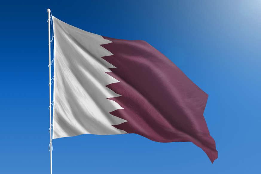 الشريحة 13 من 22: The National flag of Qatar blowing in the wind in front of a clear blue sky