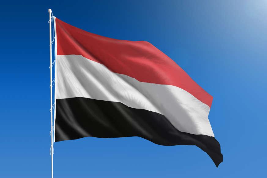 الشريحة 21 من 22: The National flag of Yemen blowing in the wind in front of a clear blue sky