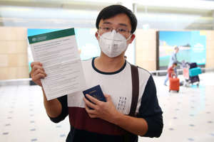 SYDNEY, AUSTRALIA - JANUARY 23: Kevin Ouyang holds up an Australian Government document pertaining to the coronavirus as passengers arrive at Sydney International Airport on January 23, 2020 in Sydney, Australia. The flight from Wuhan departed the Chinese city prior to officials temporarily closing down transport from the city to help stop the outbreak of a strain of coronavirus that has killed 17 people and infected over 500 in places as far away as the United States. Flights, trains and public transport including buses, subway and ferry services have temporarily closed in Wuhan with officials asking residents to stay in town to try and contain the flu-like virus. This week marks the start of Chinese Lunar New Year holiday, the busiest season for Chinese travellers. (Photo by Don Arnold/Getty Images)