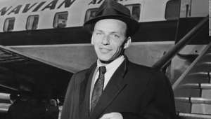 Frank Sinatra wearing a suit and tie: 13th April 1956:  Frank Sinatra (1915 - 1998), American singer and film star, arriving at an airport.  (Photo by Hulton Archive/Getty Images)