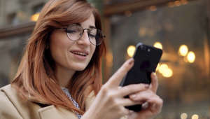 a woman wearing glasses using a cell phone